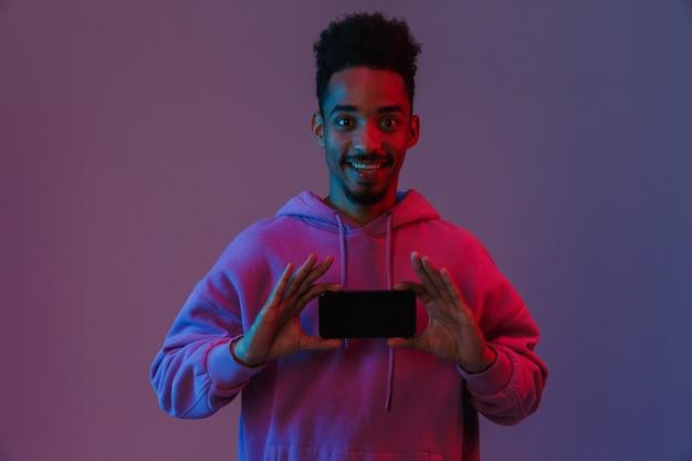 Retrato de um homem afro-americano satisfeito com um capuz colorido, sorrindo e segurando o celular isolado na parede violeta