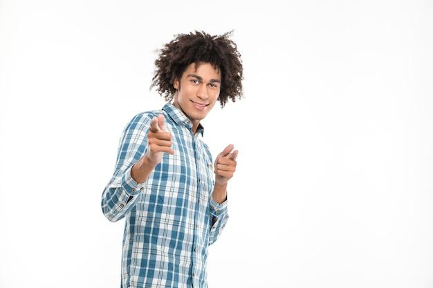 Retrato de um homem afro-americano sorridente, apontando os dedos isolados em uma parede branca.