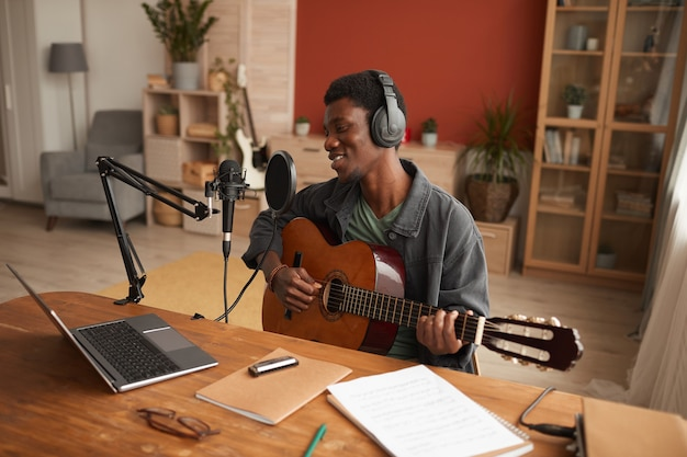 Retrato de um homem afro-americano sorridente, cantando ao microfone e tocando violão enquanto grava música no estúdio, copie o espaço
