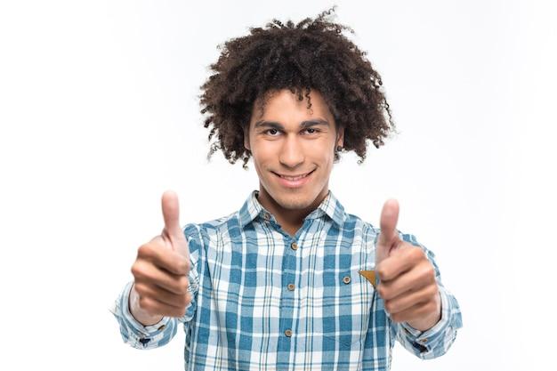 Retrato de um homem afro-americano sorridente com cabelo encaracolado aparecendo os polegares isolados em uma parede branca.