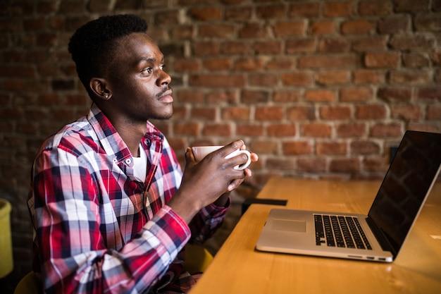 Retrato de um homem afro-americano tomando café e trabalhando em um laptop no café