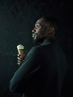 Retrato de um homem afro-americano triste segurando sorvete sobre o fundo preto do estúdio