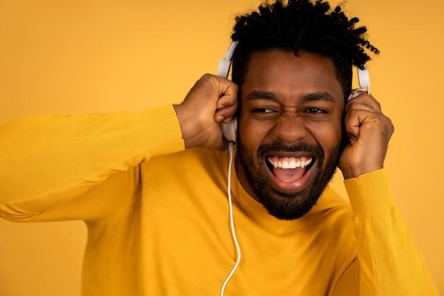 Retrato de um homem afro, curtindo ouvir música com fones de ouvido em pé contra um fundo amarelo isolado.