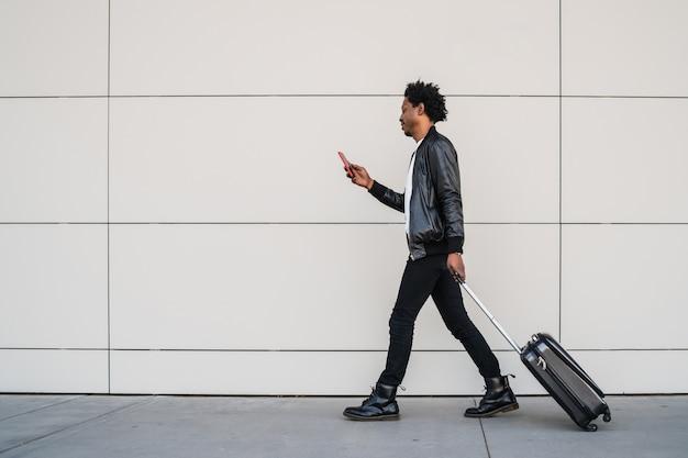 Retrato de um homem afro-turista usando seu telefone celular e carregando a mala enquanto caminha ao ar livre na rua