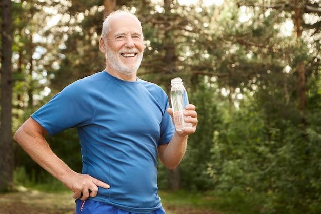 Retrato de um homem alegre aposentado caucasiano ativo com barba e cabeça em negrito, segurando a mão em sua cintura e bebendo água fresca de uma garrafa de vidro, descansando após o treino físico matinal
