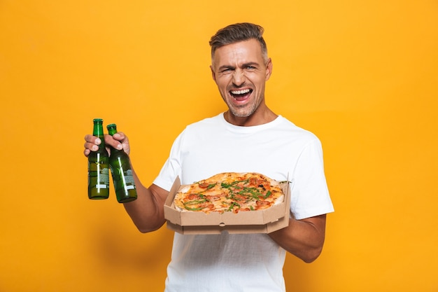 Retrato de um homem alegre de 30 anos em uma camiseta branca bebendo cerveja e comendo pizza em pé isolado no amarelo
