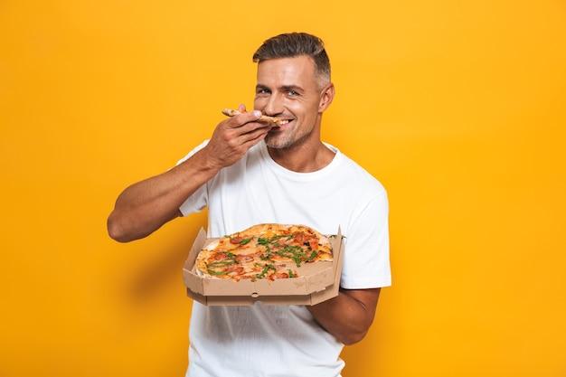 Retrato de um homem alegre de 30 anos em uma camiseta branca segurando e comendo pizza em pé isolado no amarelo