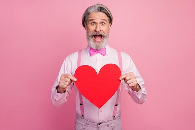 Retrato de um homem alegre e muito feliz, segurando um grande coração vermelho grande