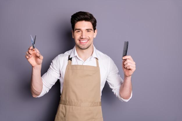 Retrato de um homem alegre e positivo, cabeleireiro segurando uma tesoura, pente profissional, pronto para cortar o cabelo, usar uma camisa branca isolada sobre a parede de cor cinza