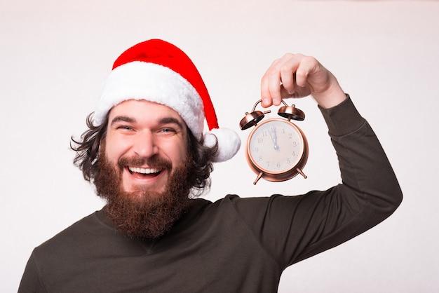 Retrato de um homem alegre e sorridente com barba usando chapéu de papai noel e segurando um despertador