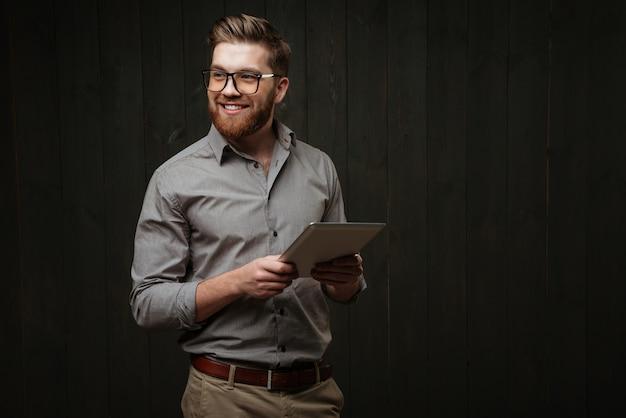 Retrato de um homem alegre e sorridente em óculos, segurando um computador tablet e olhando para longe, isolado em uma superfície de madeira preta