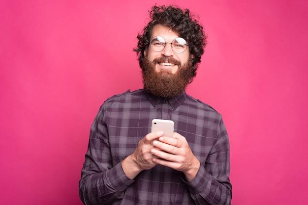 Retrato de um homem alegre hippie barbudo usando óculos redondos, segurando um smartphone e parecendo confiante