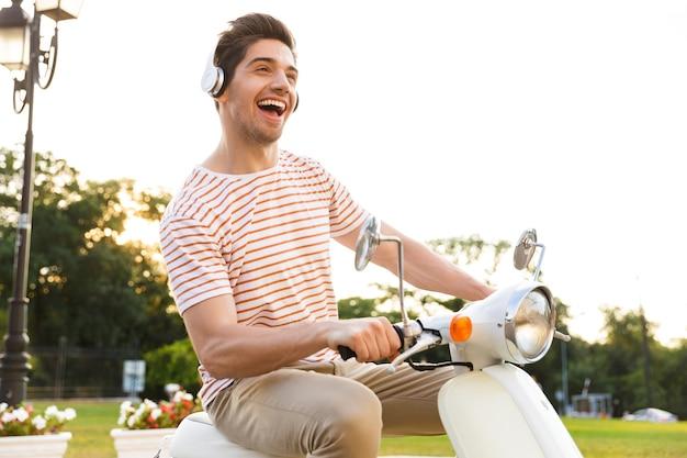 Retrato de um homem alegre, usando fones de ouvido, sorrindo e andando de moto pelas ruas da cidade