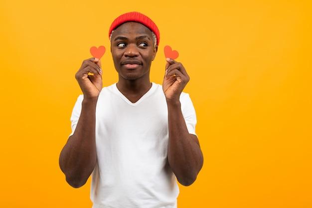 Retrato de um homem americano bonito de pele escura em uma camiseta branca segurando dois pequenos cartões postais em forma de coração para dia dos namorados e olhando para o lado em um fundo amarelo