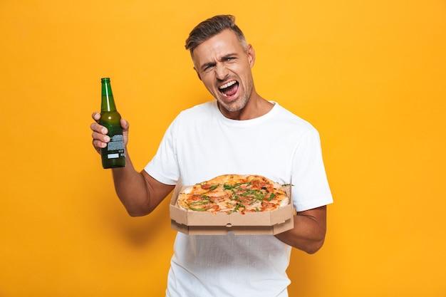 Retrato de um homem animado de 30 anos em uma camiseta branca bebendo cerveja e comendo pizza em pé isolado no amarelo