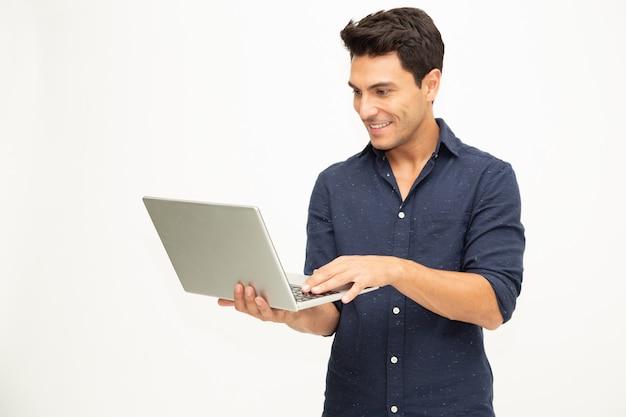 Retrato de um homem animado, segurando o computador portátil e comemorando o sucesso em branco