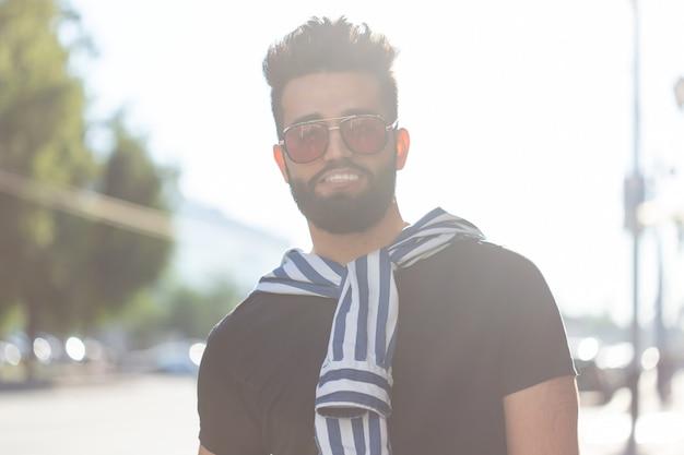 Retrato de um homem árabe elegante jovem hippie com suco. férias urbanas no conceito de fim de semana.