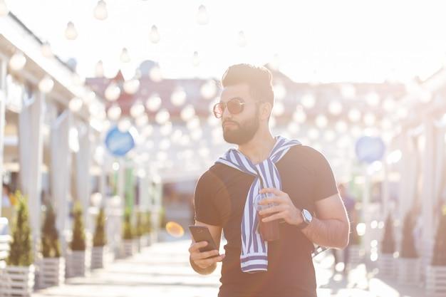 Retrato de um homem árabe jovem alegre positivo com um copo de suco com um canudo enquanto caminhava no parque em um dia quente de verão ensolarado. o conceito de descanso após estudo e trabalho nos fins de semana.