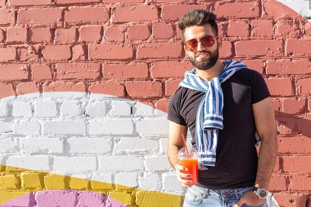 Retrato de um homem árabe jovem alegre positivo com um copo de suco com um canudo, enquanto caminhava pela cidade em um dia quente de verão ensolarado. o conceito de descanso após estudo e trabalho nos fins de semana.