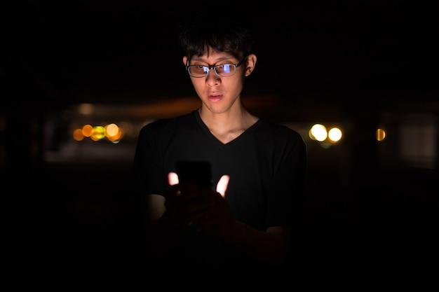 Retrato de um homem asiático ao ar livre à noite em um estacionamento usando a turba