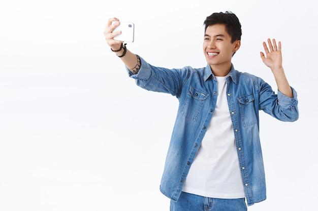 Retrato de um homem asiático bonito e amigável acenando para a câmera do smartphone para dizer oi família durante uma videochamada durante a quarentena, distanciando-se em casa
