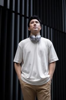 Retrato de um homem asiático bonito posando ao ar livre na cidade com fones de ouvido