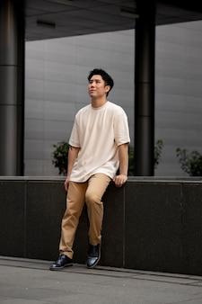 Retrato de um homem asiático bonito posando ao ar livre na cidade