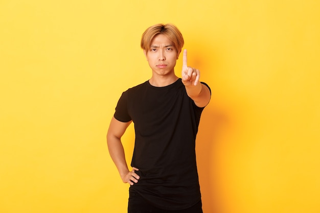 Retrato de um homem asiático desapontado e sério balançando o dedo para repreender alguém, parado na parede amarela