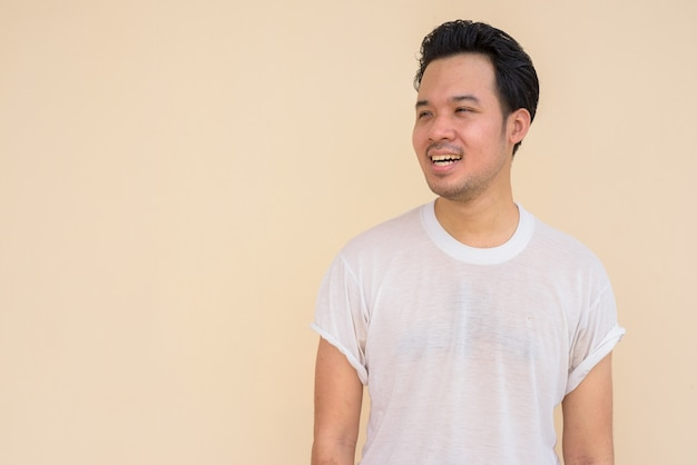 Retrato de um homem asiático feliz vestindo uma camiseta branca contra um fundo liso ao ar livre enquanto pensa