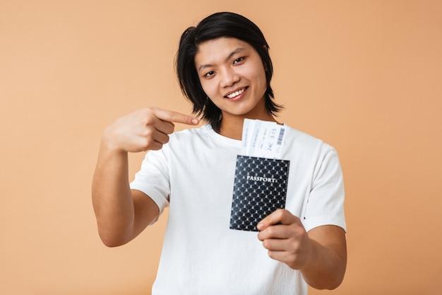 Retrato de um homem asiático feliz vestindo uma camiseta em pé, isolado sobre uma parede bege, mostrando o passaporte com as passagens aéreas