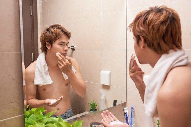 Retrato de um homem asiático lavando no banheiro