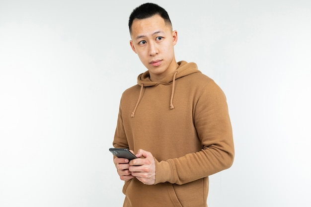 Retrato de um homem asiático sério com capuz casual com um smartphone nas mãos, sobre um fundo branco com espaço de cópia