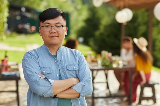 Retrato de um homem asiático sorridente posando ao ar livre no verão com amigos e familiares, jantando no terraço