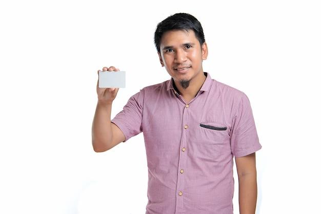 Retrato de um homem asiático sorridente segurando um cartão branco em branco sobre fundo branco