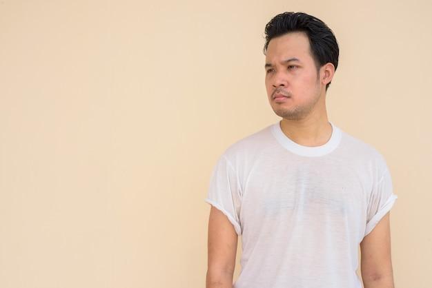 Retrato de um homem asiático vestindo uma camiseta branca contra um fundo liso ao ar livre enquanto pensa