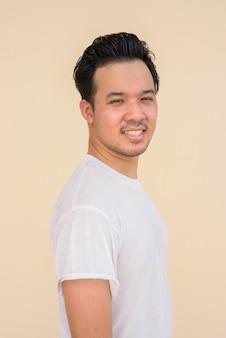 Retrato de um homem asiático vestindo uma camiseta branca contra um fundo liso ao ar livre enquanto sorri
