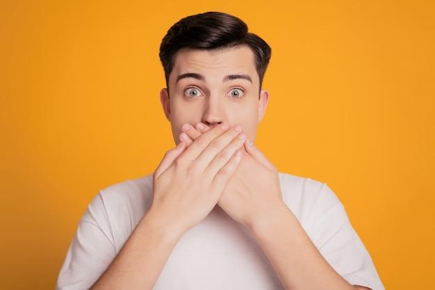 Retrato de um homem assustado com uma camiseta branca cobrindo a boca com a mão em um fundo amarelo