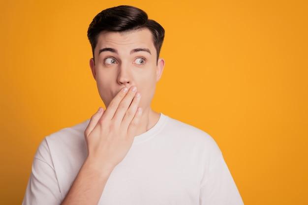 Retrato de um homem assustado com uma camiseta branca cobrindo a boca com a mão parece um fundo de espaço vazio amarelo