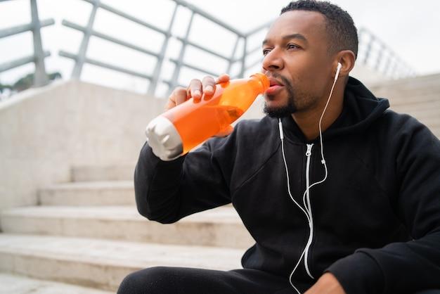 Retrato de um homem atlético bebendo algo após o treino enquanto está sentado na escada de concreto. esporte e estilo de vida saudável.