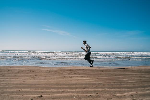 Retrato de um homem atlético correndo na praia. esporte, fitness e estilo de vida saudável.