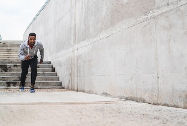 Retrato de um homem atlético correndo na rua contra um fundo cinza. esporte e estilo de vida saudável.