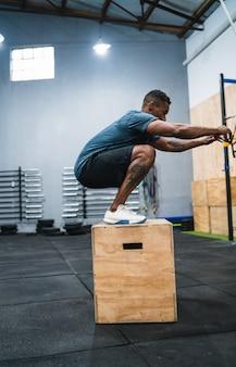 Retrato de um homem atlético, fazendo exercícios de salto de caixa. crossfit, esporte e conceito de estilo de vida saudável.