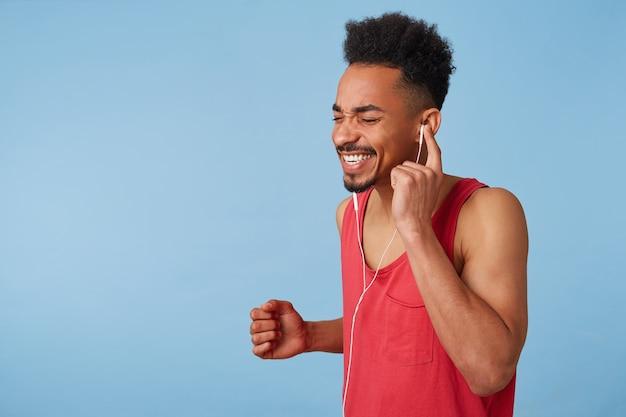 Retrato de um homem atraente afro-americano feliz com uma camisa vermelha ouve boa música, canta e dança em voz alta, segura o fone de ouvido com a mão esquerda, fecha os olhos, fica de pé.