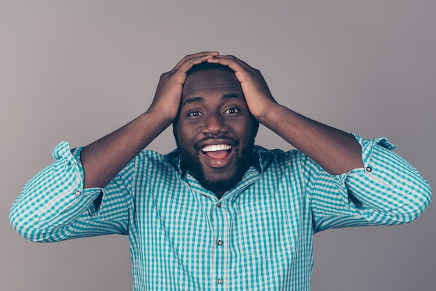 Retrato de um homem barbudo afro-americano animado e feliz, segurando a cabeça e a boca aberta