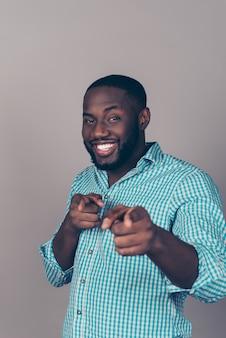 Retrato de um homem barbudo afro-americano feliz e animado apontando para a câmera
