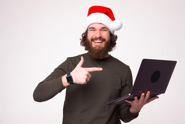 Retrato de um homem barbudo alegre com chapéu de papai noel apontando para o laptop na parede branca