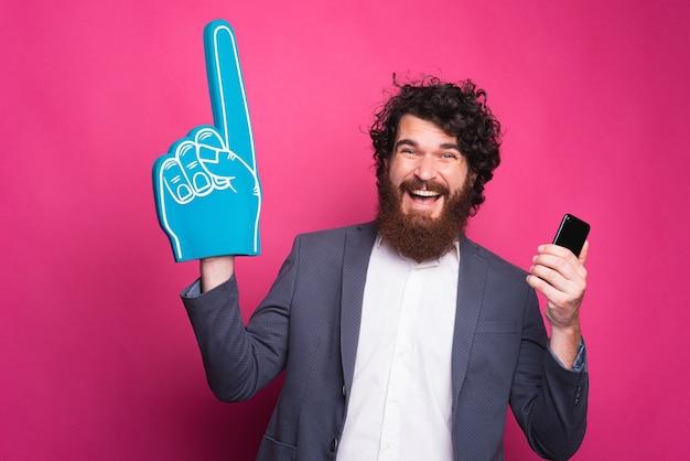Retrato de um homem barbudo alegre em terno segurando um smartphone e apontando com uma luva em leque