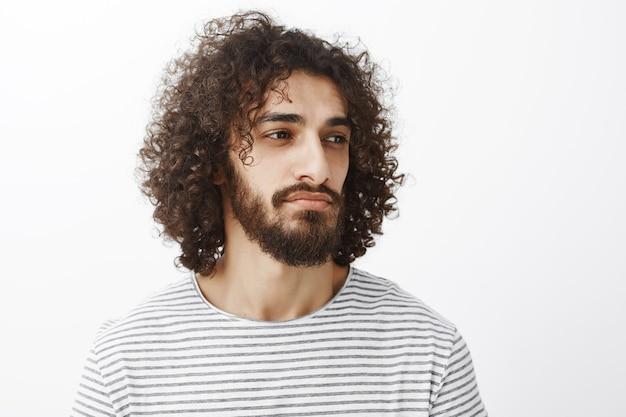 Retrato de um homem barbudo atraente deamy inteligente com cabelo encaracolado, olhando bem enquanto pensa ou se distraindo com um leve sorriso