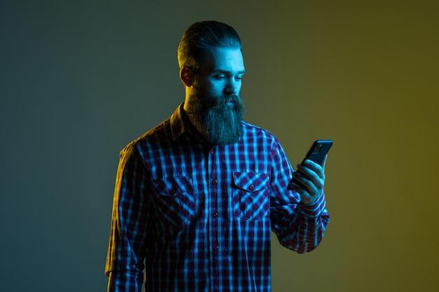 Retrato de um homem barbudo atraente e bonito com fones de ouvido segurando o telefone móvel isolado no espaço claro