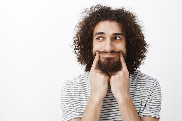 Retrato de um homem barbudo atraente e estressado, com cabelo encaracolado, sorrindo com o dedo indicador e olhando para a esquerda com expressões tristes, entediado